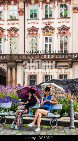 A couple of female tourists take a rest in front of the National Gallery in the Kinský Palace in Old Town Square, - Stock Photo