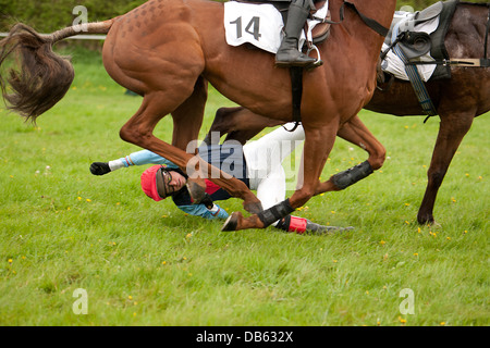 Horse riding jockey being dragged along by the horse along the race track - Stock Photo