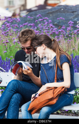 A couple of young tourists look at the Lonely Planet guide book in Prague. - Stock Photo