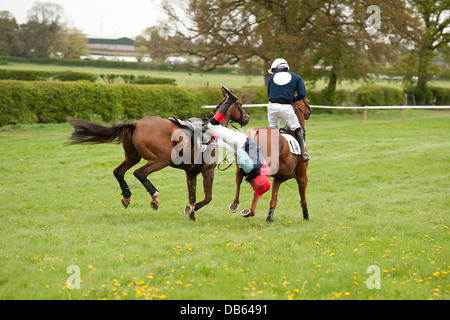 Jockey being dragged along by a horse during a race - Stock Photo