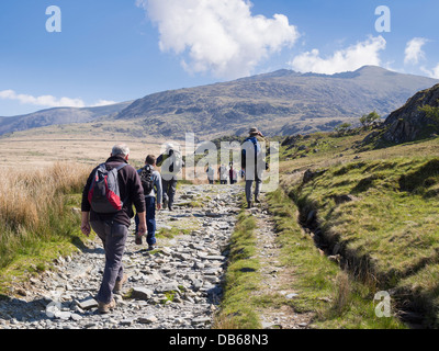 Ramblers walking on Rhyd Ddu path up to Mount Snowdon with a view to peak in distance in Snowdonia. Rhyd Ddu, North - Stock Photo