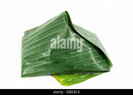 coconut rice 'nasi lemak' with sambal chilli wrap in banana leaves - Stock Photo