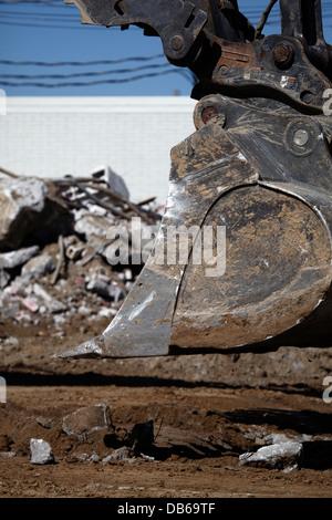 Excavator bucket near debris pile. - Stock Photo