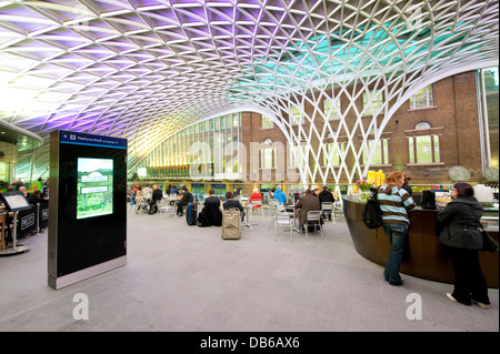 People taking a break in the Western concourse area of Kings Cross Railway Station, London, England. - Stock Photo