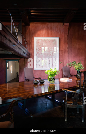 Polished wood table with artwork in Antwerp apartment of Boris Vervoordt - Stock Photo