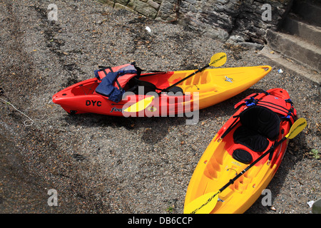 Brightly coloured kayaks on riverbank. - Stock Photo