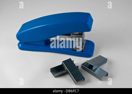 Blue stapler and staples on a light background. - Stock Photo