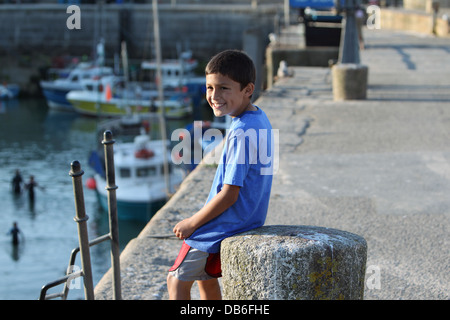Young Hispanic boy smiles while sitting on a concrete bollard on an old harbor wall - Stock Photo