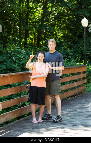 Vertical photo of young girl, holding up small trout, and her father fishing off wooden bridge with trees and lamp - Stock Photo