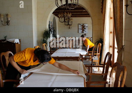 Workers preparing a dining room in Kempinski San Lawrenz the largest hotel in Gozo the sister island of Malta - Stock Photo