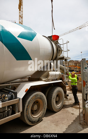construction workers pouring concrete from delivery truck building site ongoing in Barcelona Catalonia Spain - Stock Photo