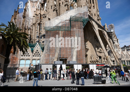 tourists and visitors queue to enter the Sagrada Familia Barcelona Catalonia Spain - Stock Photo
