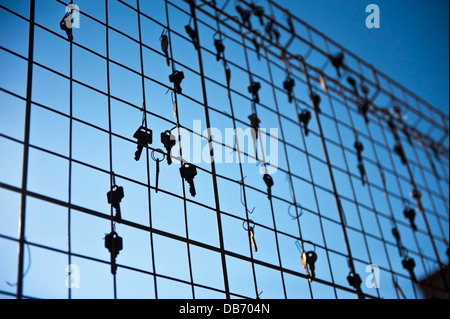 Keys hooked to a metal grid type fence at dusk - Stock Photo