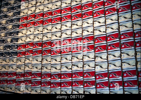 Converse Chuck Taylor All Stars tennis shoes displayed on the wall at the Converse Shoe store in New York City - Stock Photo