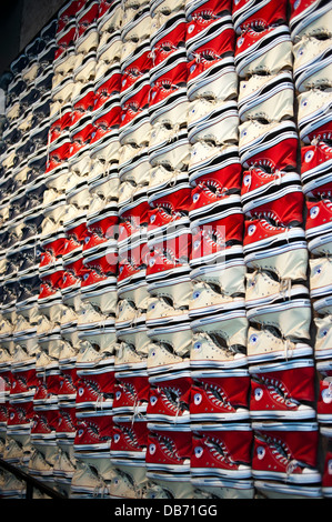 Converse Chuck Taylor All Stars tennis shoes on the wall at the Converse Shoe store in New York City - Stock Photo