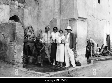 tourism, German tourists posing for souvenir photo in front of public fountain, full length, Marrakech, June 1937, - Stock Photo