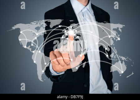 Portrait of handsome businessman touching a world map on the screen showing global connection between different - Stock Photo