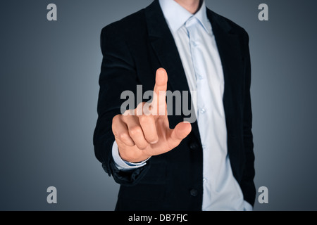 Portrait of handsome businessman touching a blank invisible screen. Touch screen concept image. Isolated on dark - Stock Photo