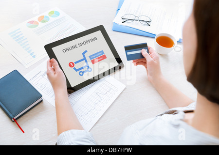 Caucasian businesswoman sitting at the desk in the office and using credit card and modern digital tablet for online - Stock Photo