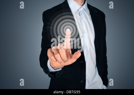 Portrait of business person touching button on invisible screen. Touch screen concept image. Isolated on dark gray - Stock Photo