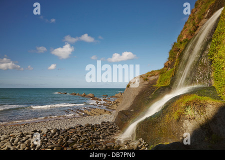 Waterfall onto the beach at Blegberry, just north of Hartland Quay, Devon, Great Britain. - Stock Photo