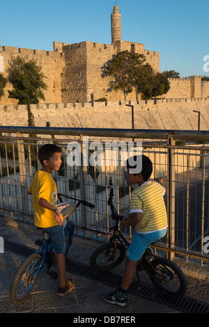 Two young palestinian boys on bicycles with Tower of David in background.Jaffa Gate. Jerusalem Old City. Israel. - Stock Photo