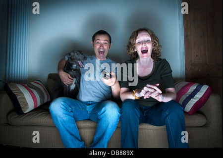 middle aged couple and dog watching the television laughing - Stock Photo