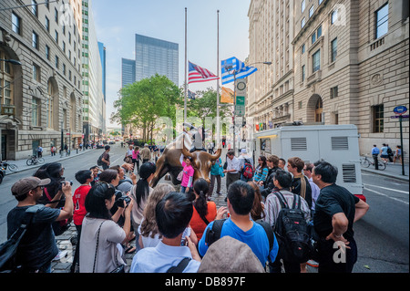 A crowd of people pose and take photographs at the Wall Street Charging Bull in NYC - Stock Photo