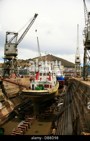 a ship undergoes repairs in the dry dock at Cape Town's harbour. - Stock Photo