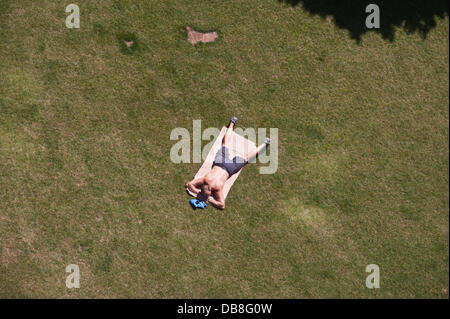 London, UK - 25 July 2013: People enjoy the sun in the park next to City Hall as heatwave continues to hit the UK - Stock Photo