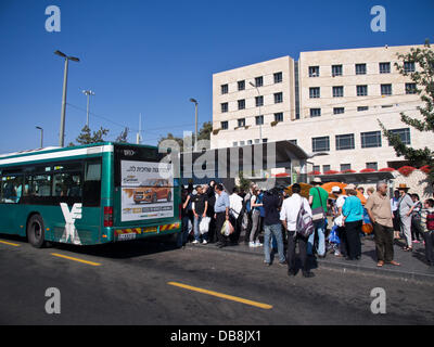 Jerusalem, Israel. 25-July-2013. A bus stops to pick up passengers at a crowded stop offering little shade from - Stock Photo