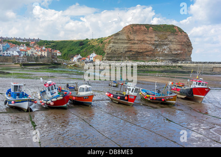 A line of fishing boats lie on the sand at low tide in Staithes Harbour North Yorkshire in front of Cowbar Nab cliff - Stock Photo