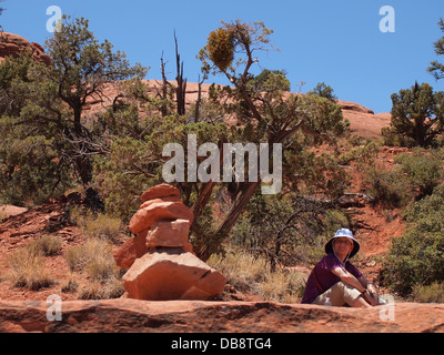 Woman tourist rests during a hike at Belll Rock, a balanced (both masculine and feminine) energy vortex, in Sedona, - Stock Photo