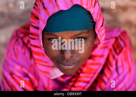 A Somali girl poses for the first picture of her life.  She lives in a small village located on the border with - Stock Photo