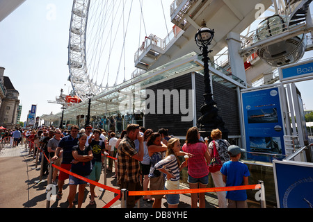 tourists queue to get into the london eye tourist attraction London England UK - Stock Photo