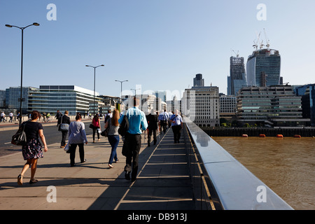 commuters and city workers cross london bridge over the river thames in the morning central London England UK - Stock Photo