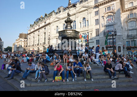 tourists and visitors sit on the steps of the eros statue in picadilly circus London England UK - Stock Photo