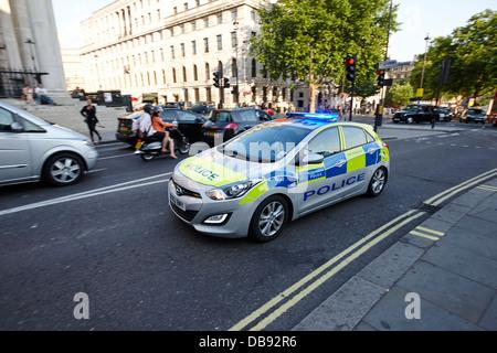 metropolitan police patrol car speeding through streets with blue lights on London England UK - Stock Photo