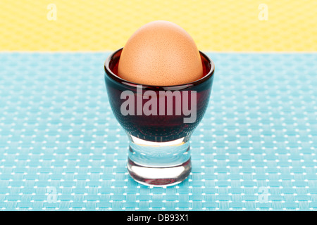 Single brown egg in eggcup on blue tablemat. - Stock Photo