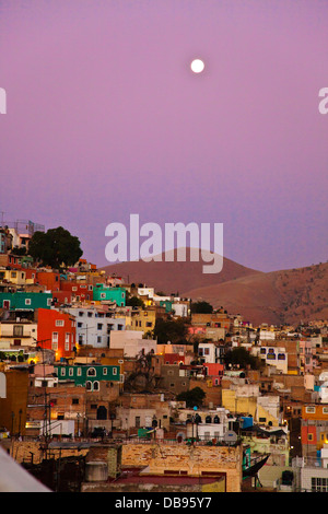 The full MOON rises over the colorful houses on the hillside of the cultural city of GUANAJUATO in central MEXICO - Stock Photo