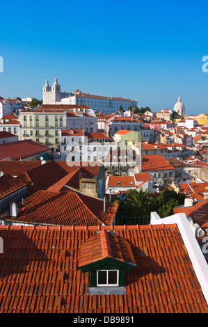 Sunny summer afternoon in Alfama District, Lisbon with monastery of Sao Vicente de Fora on the top of the hill. - Stock Photo