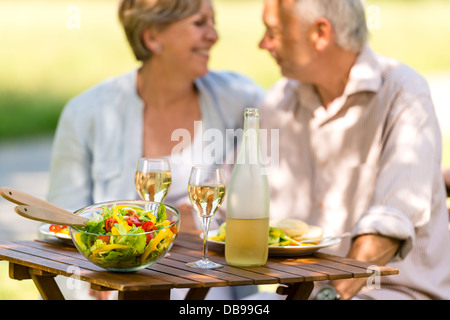 Cheerful senior citizens dating and eating outdoors - Stock Photo