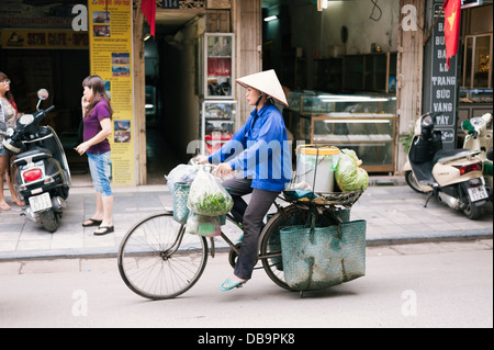 Hanoi, Vietnam - street vendor on a bicycle in the Old Quarter - Stock Photo