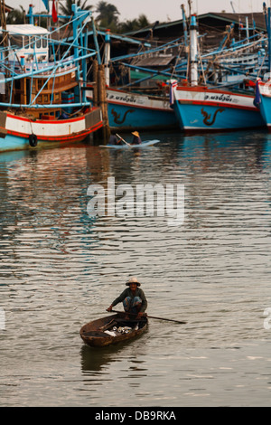 Two natives paddle small flat low narrow boats around the fishing village harbor on in Chumpon, Thailand Asia - Stock Photo
