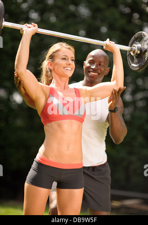 Woman with personal trainer lifting weights during outdoor exercise programme - Stock Photo