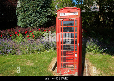 Traditional red phone kiosk in Yorkshire with laid out garden - Stock Photo