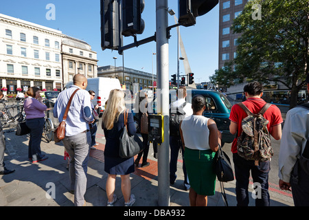 early morning commuters waiting to cross the road pedestrian crossing London England UK - Stock Photo