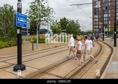 People crossing a tramway in MediaCity, Salford Quays, Manchester. - Stock Photo