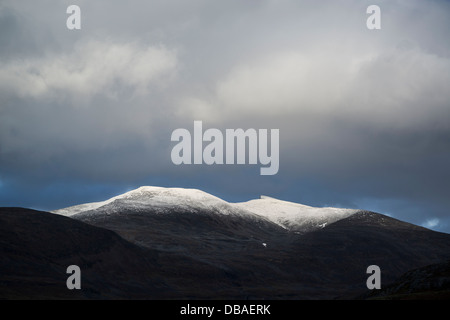 Dramatic mountain light over snow covered peak from Alesjaure mountain huti, Kungsleden trail, Lappland, Sweden - Stock Photo