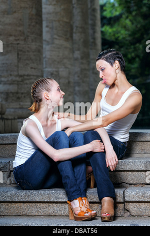 Family, mother and daughter sit and chat on the steps of the library - Stock Photo